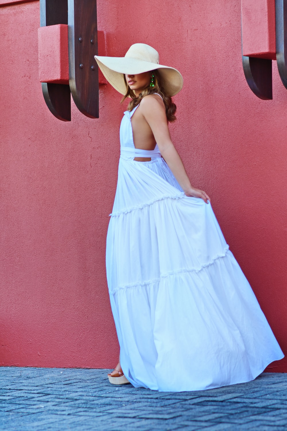 woman in blue and white sleeveless dress wearing yellow sun hat
