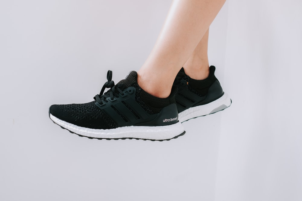 person wearing black and white nike athletic shoes