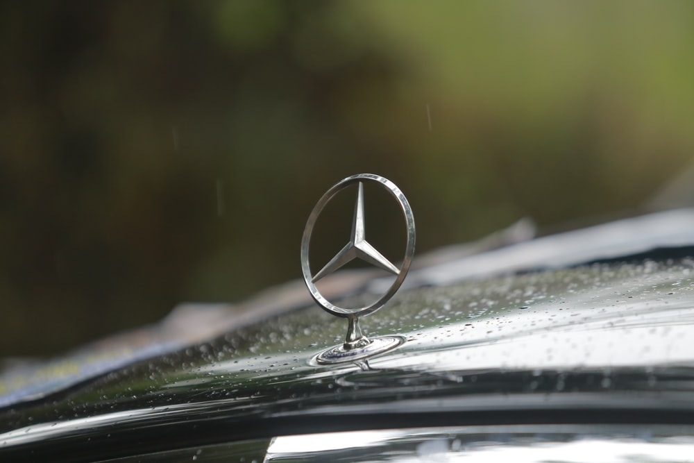 silver mercedes benz emblem on car