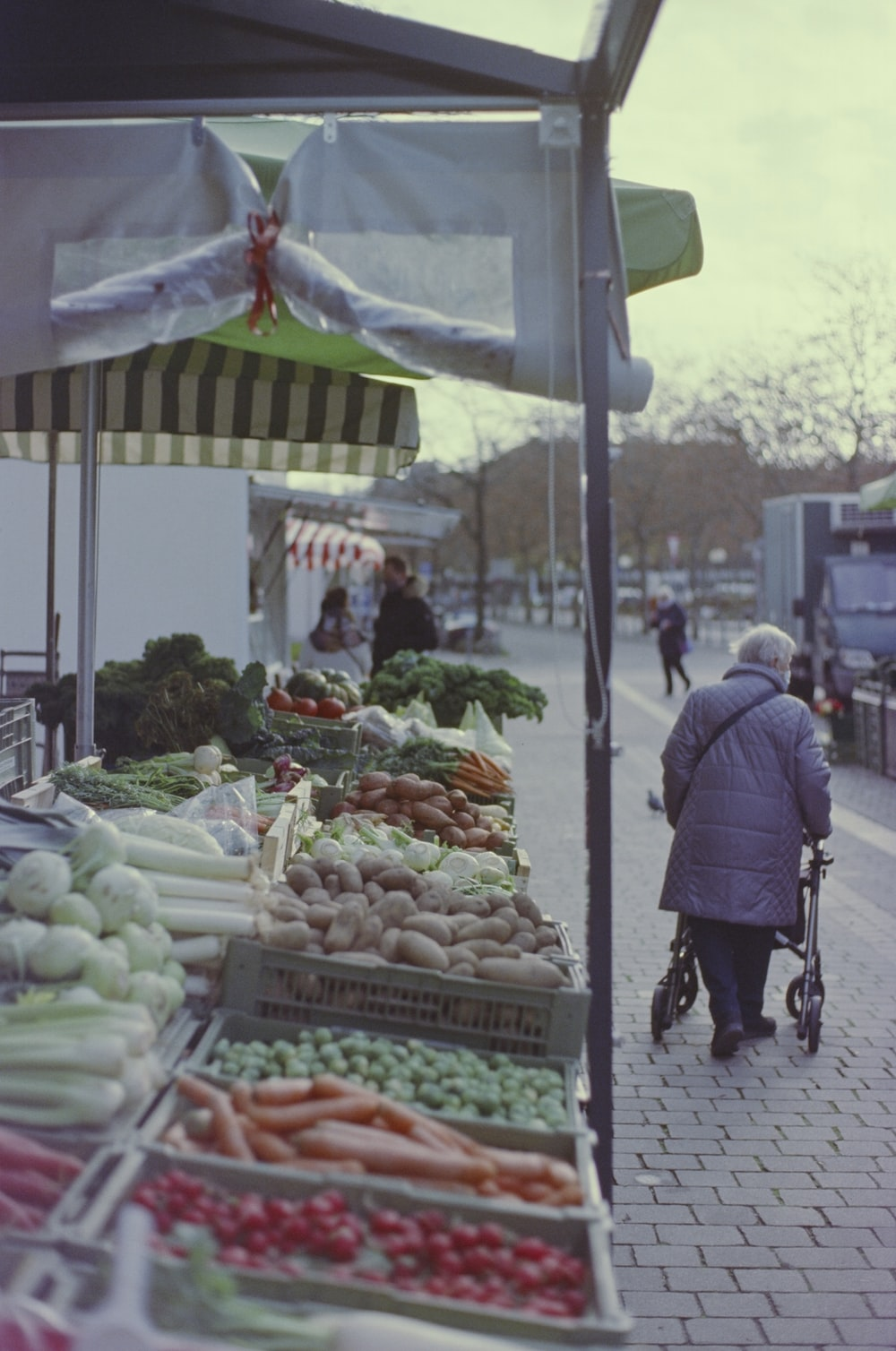 man in black jacket standing in front of vegetable stand