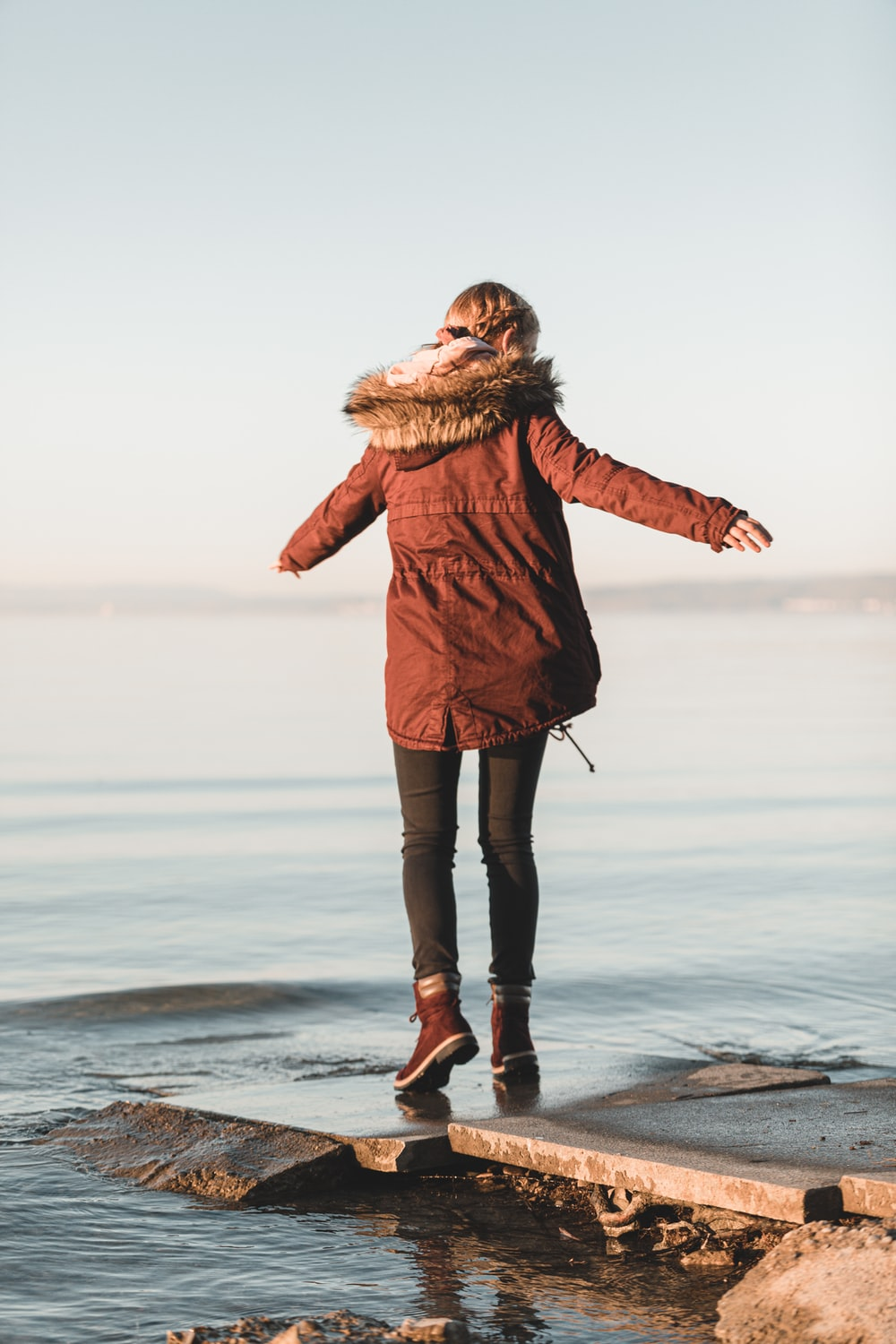 woman in brown coat standing on seashore during daytime