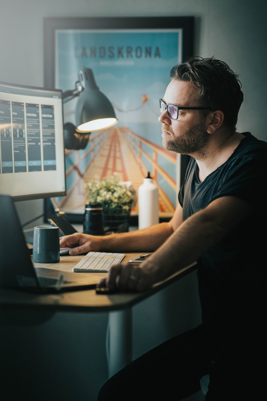 man in black crew neck t-shirt wearing black framed eyeglasses using computer