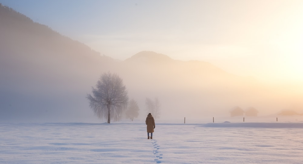 person walking on snow covered field during daytime
