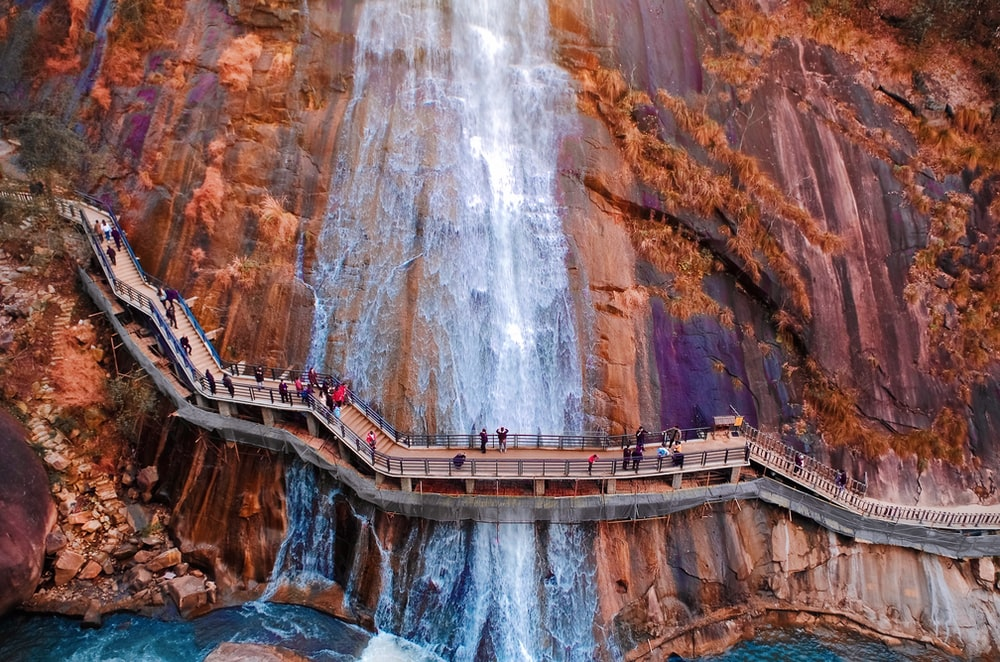 people walking on brown wooden bridge over waterfalls during daytime