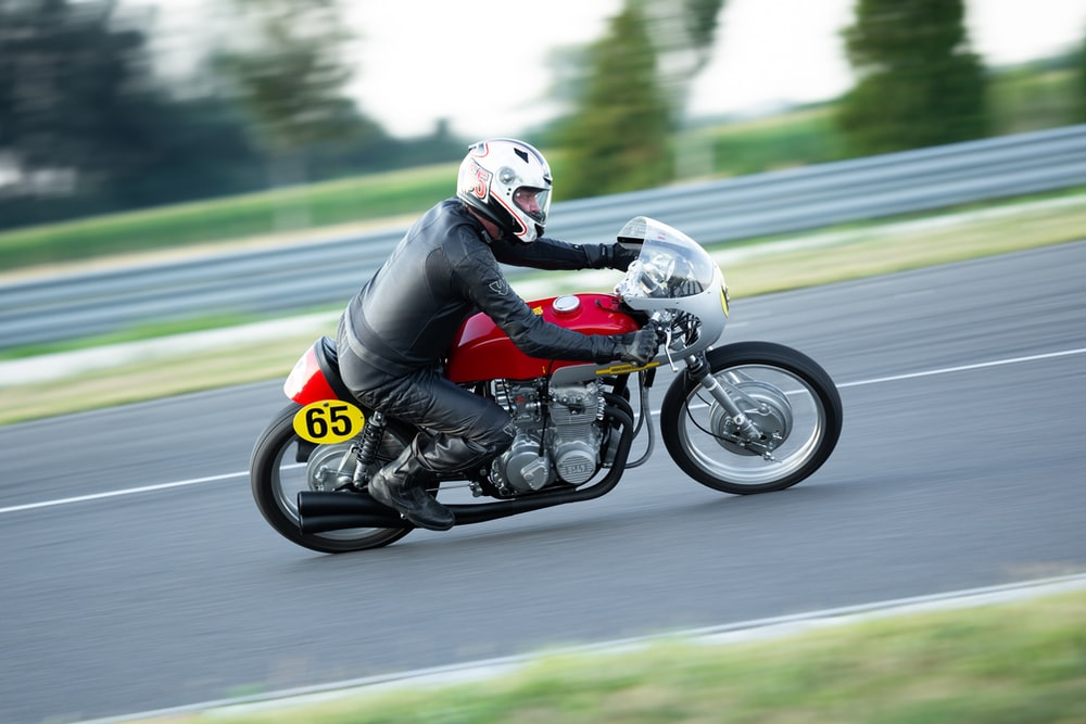 man in black and red motorcycle helmet riding on black and red sports bike on road