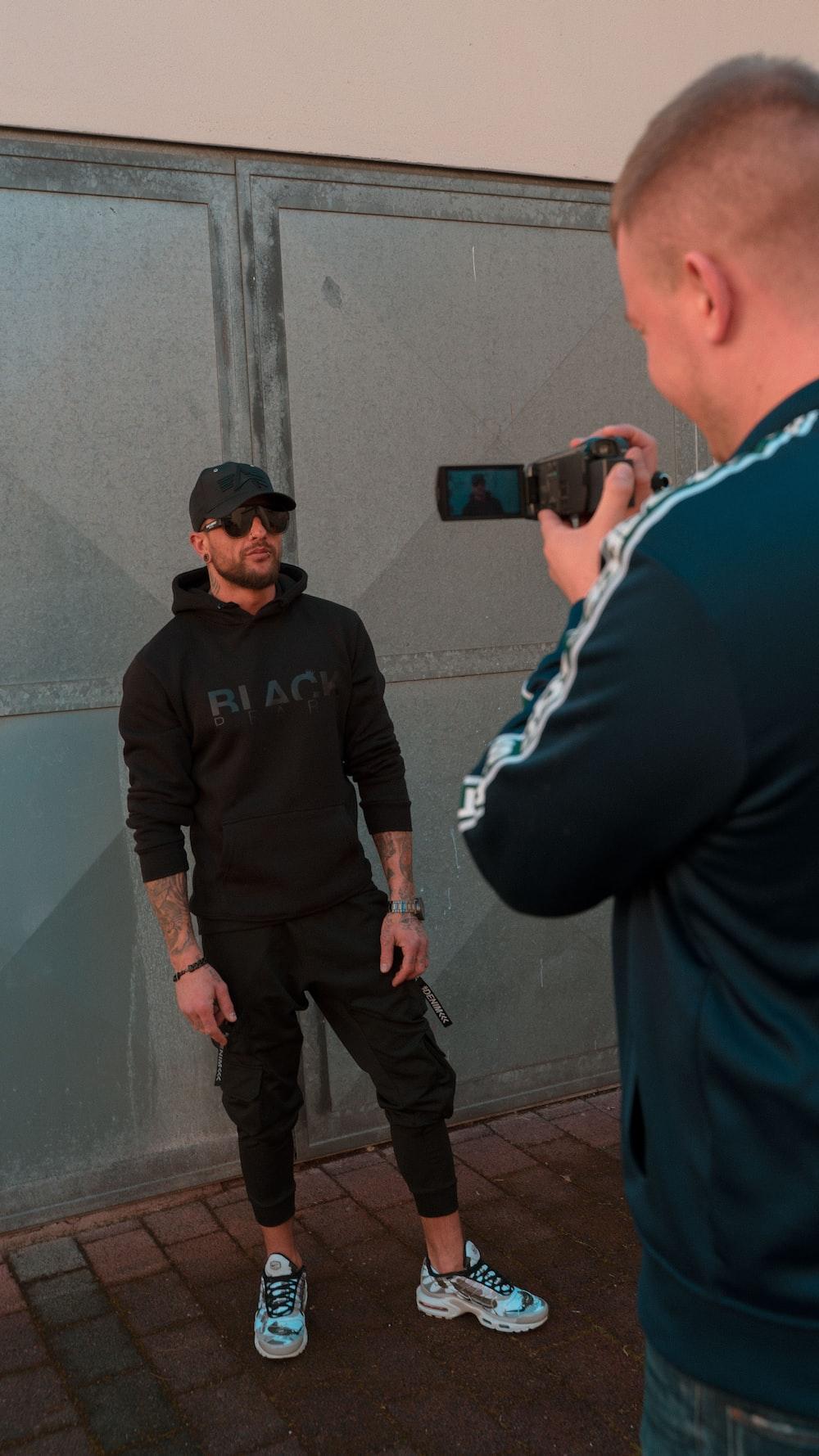 man in black sweater standing beside man in black jacket