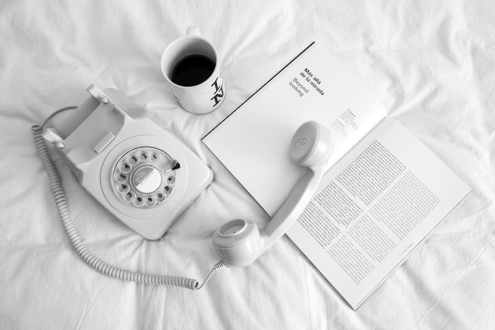 white rotary phone beside white ceramic mug