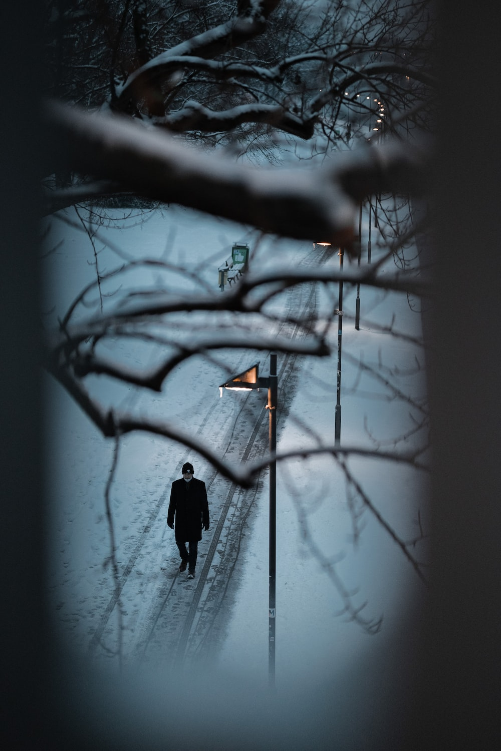 person in black jacket standing on snow covered ground