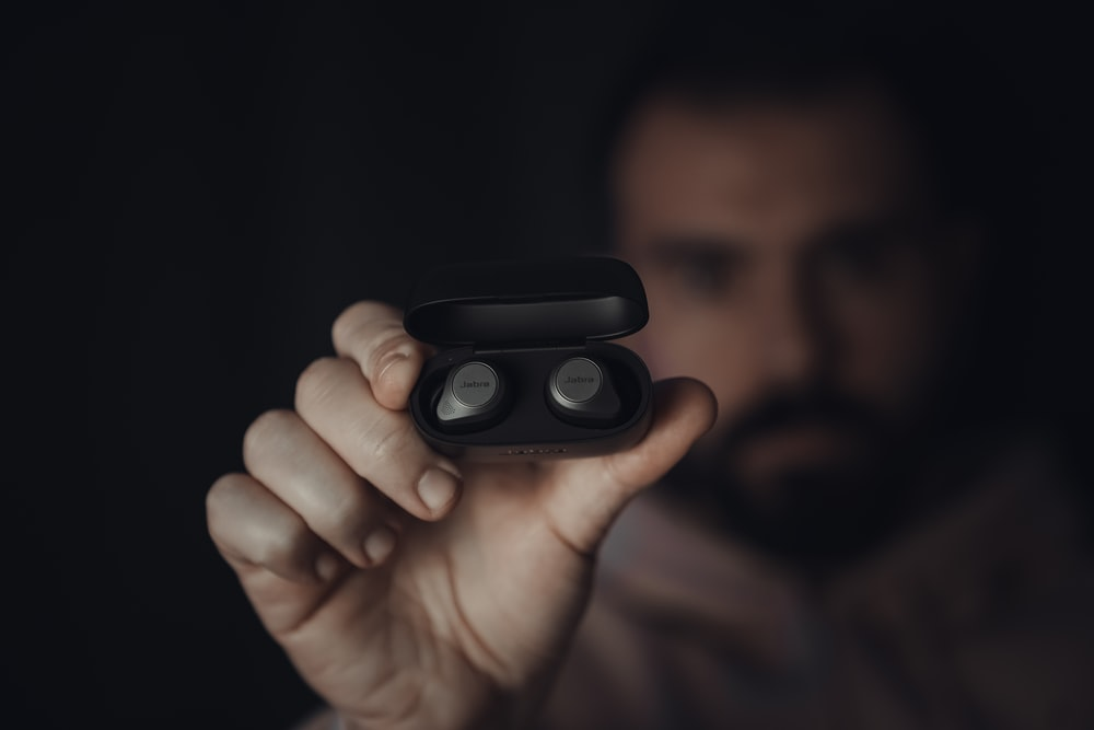 person holding black round device