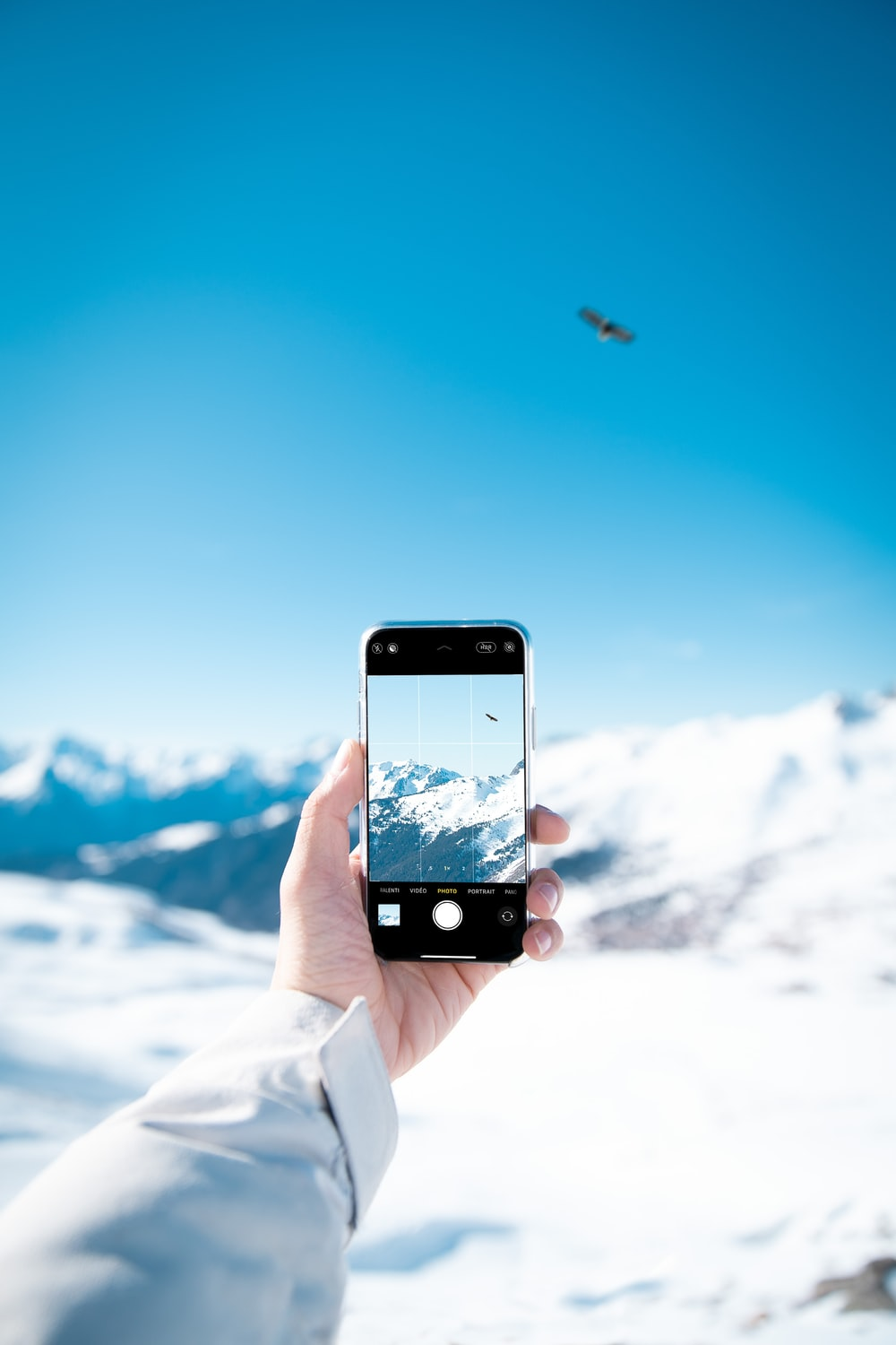 person taking photo of snow covered mountain during daytime