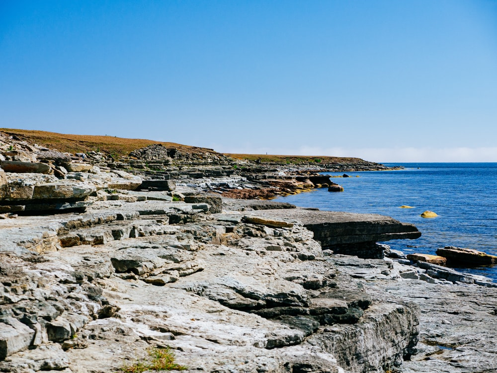gray rocky shore near blue sea under blue sky during daytime