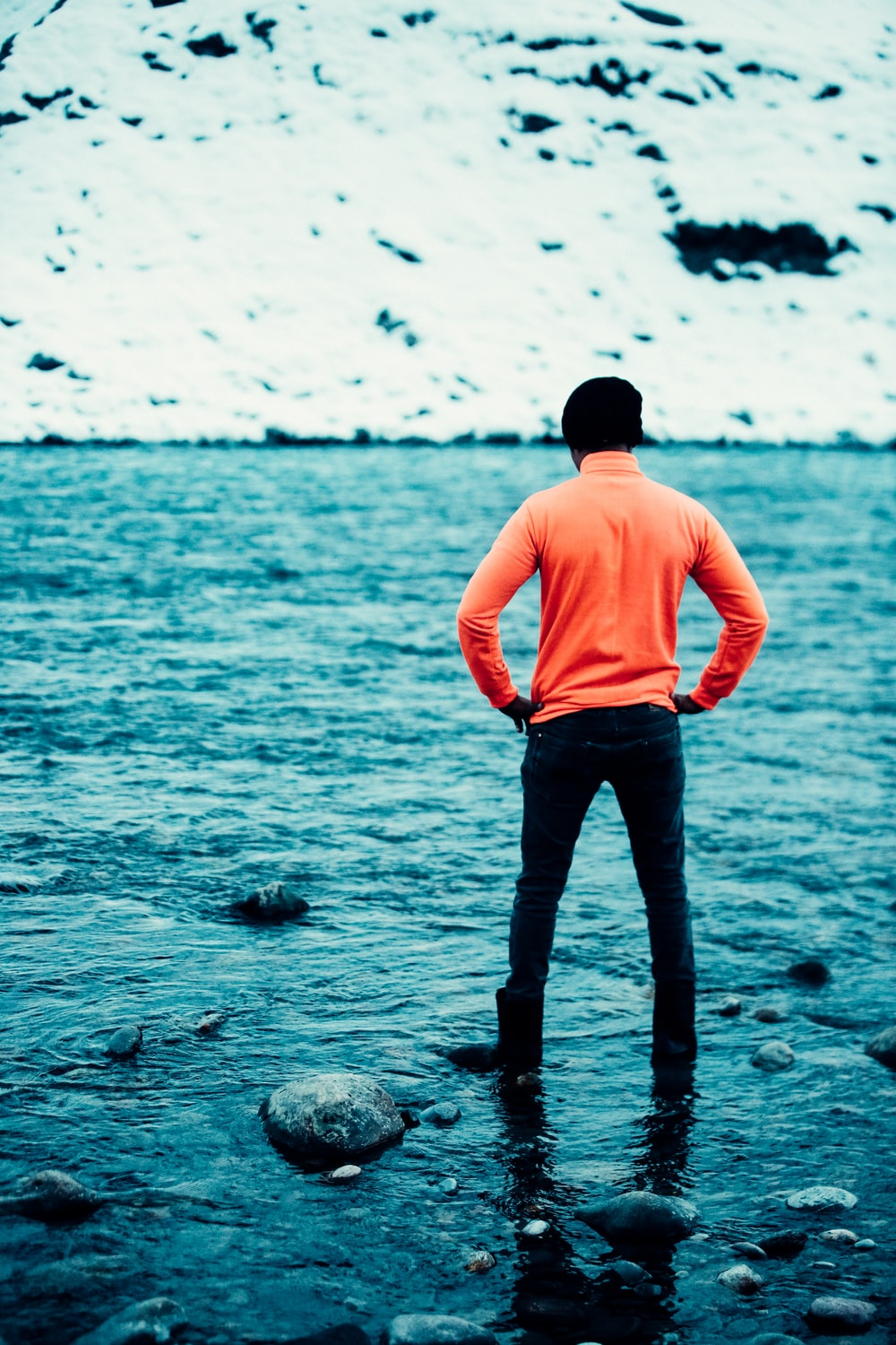 man in pink shirt and black pants standing on rocky shore during daytime