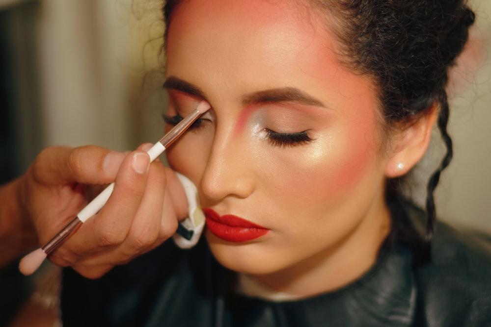 woman in red lipstick holding white cigarette stick