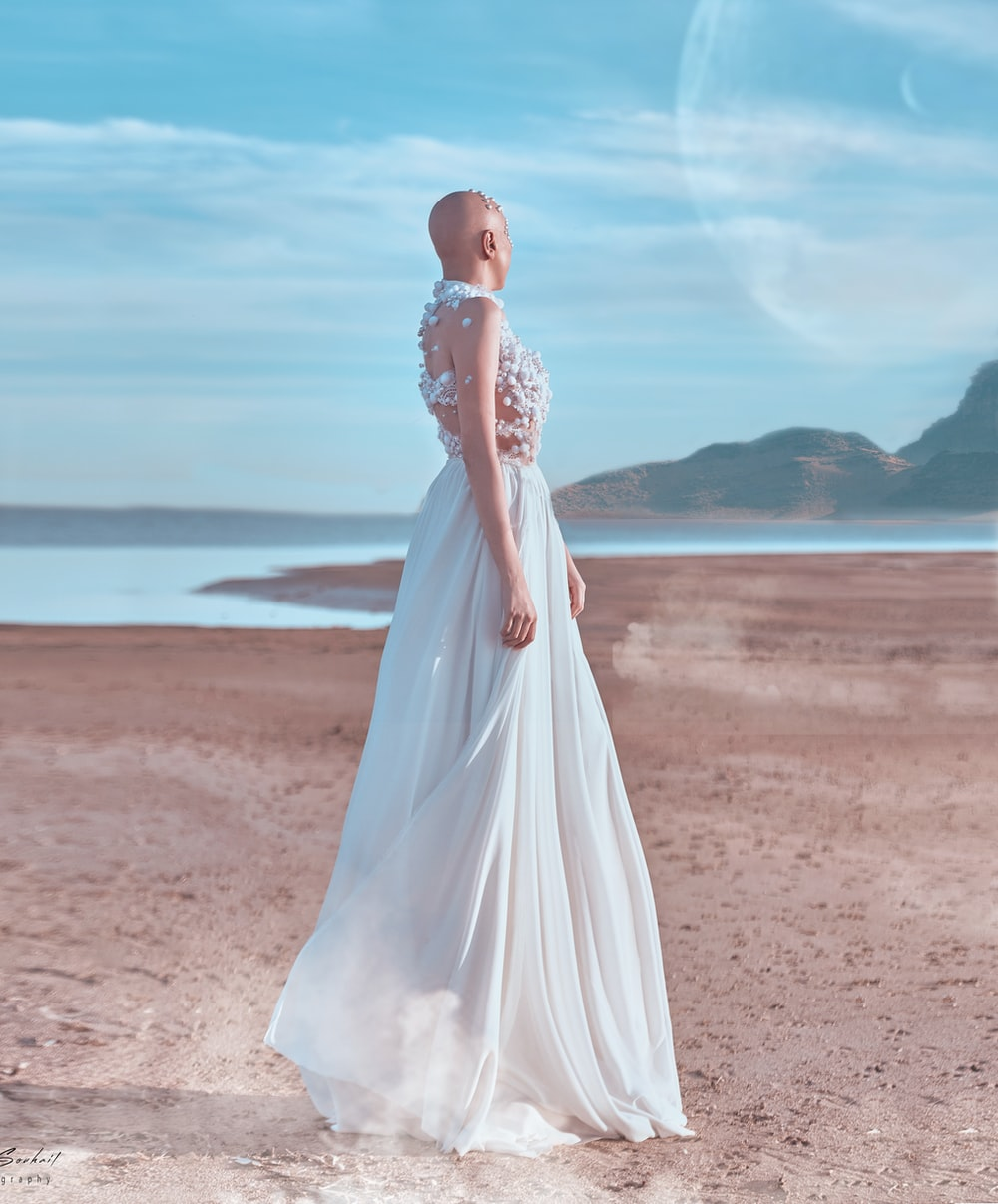 woman in white wedding dress standing on brown sand during daytime