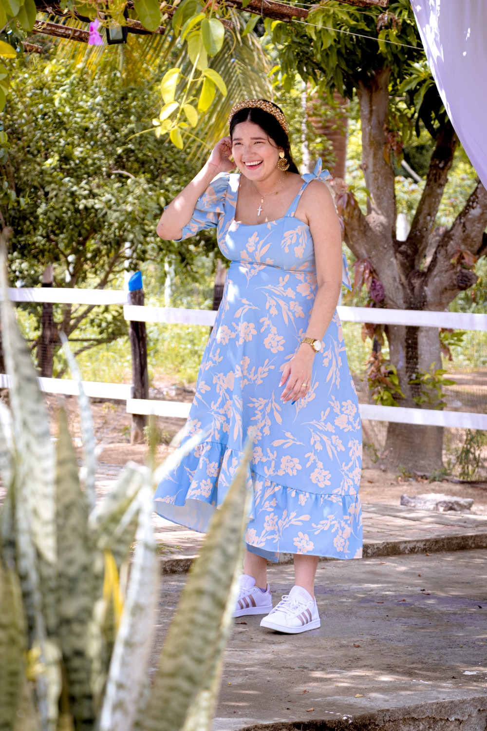 woman in blue and white floral sleeveless dress standing on wooden bridge during daytime