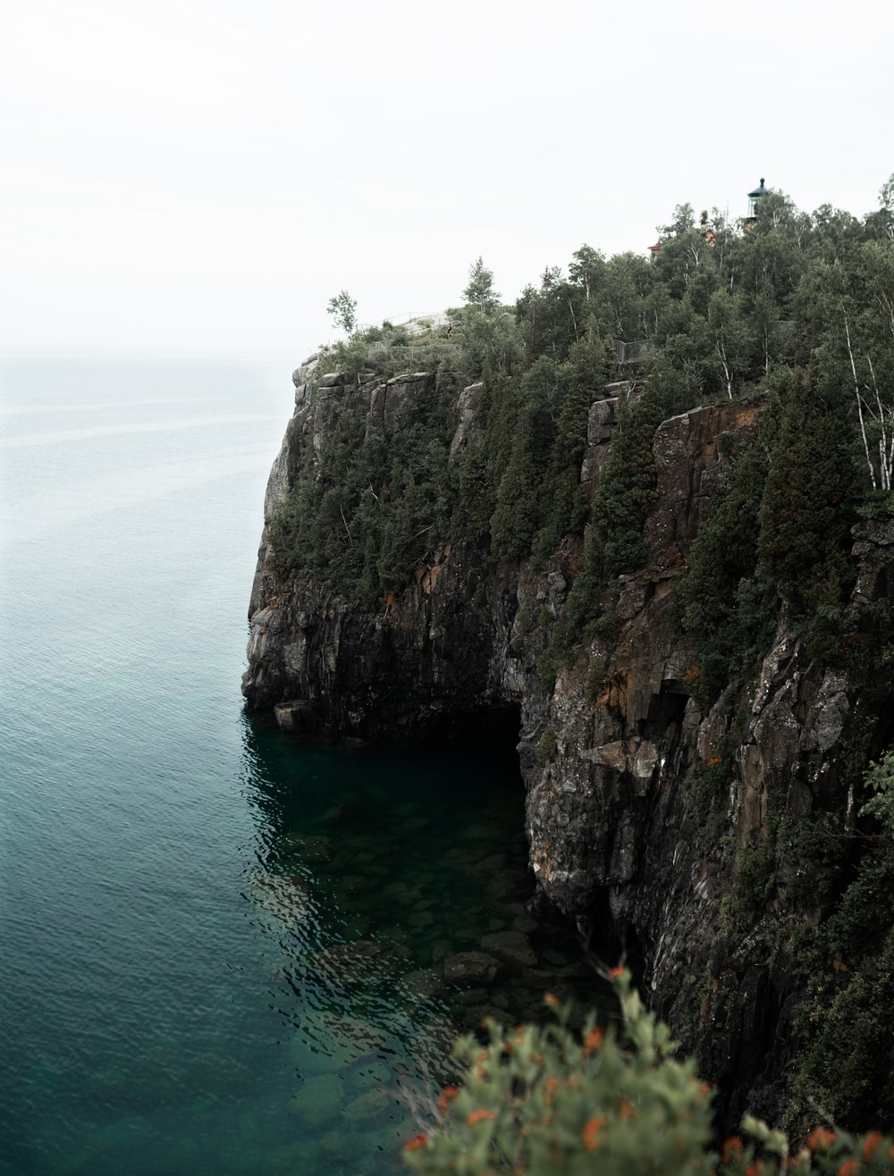 brown and green cliff beside body of water during daytime