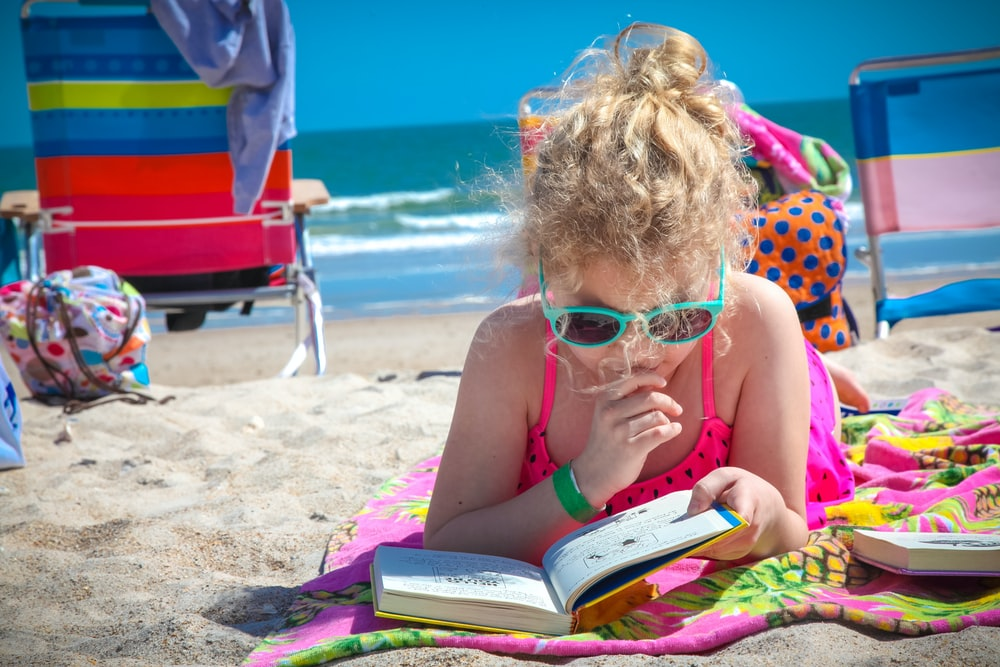 girl in pink tank top wearing eyeglasses reading book on beach during daytime
