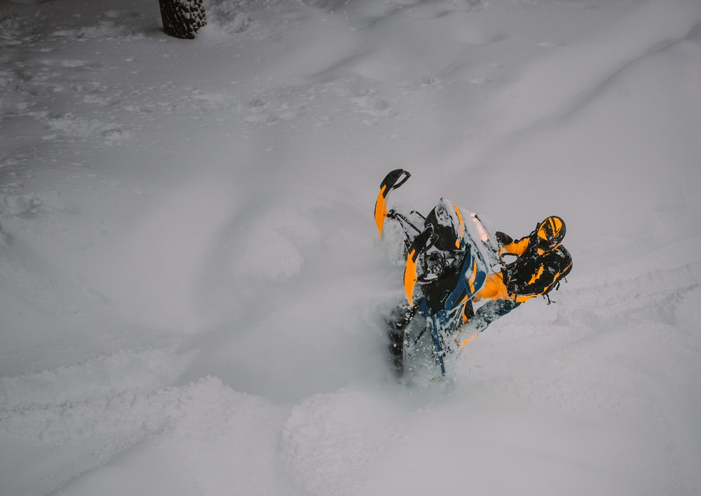 black and yellow snow mobile on snow covered ground