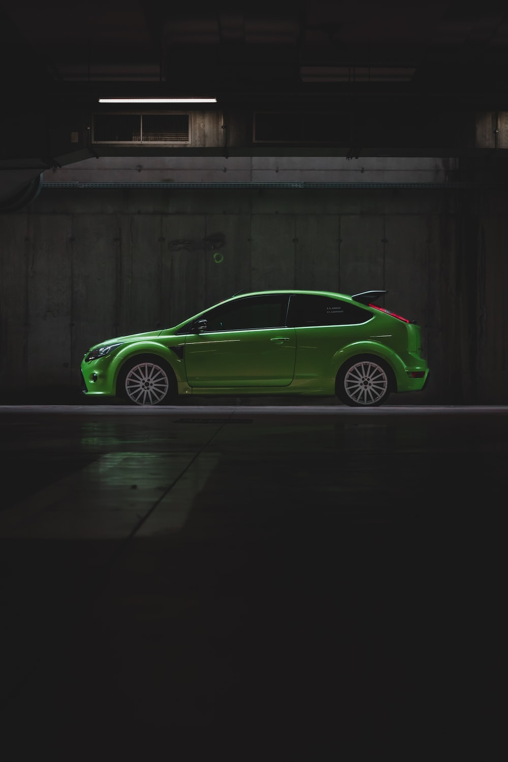 green coupe parked beside brown wooden wall