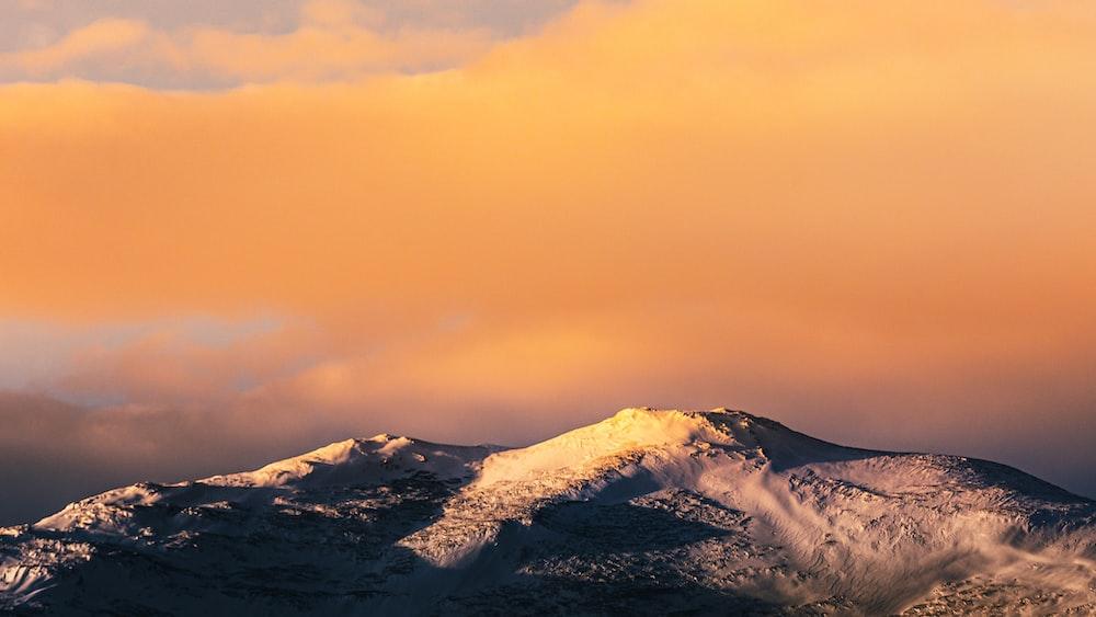 snow covered mountain under orange sky