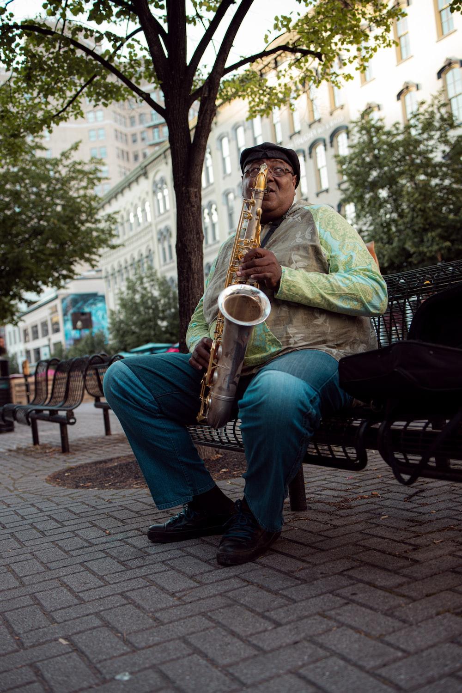 man in green dress shirt playing saxophone