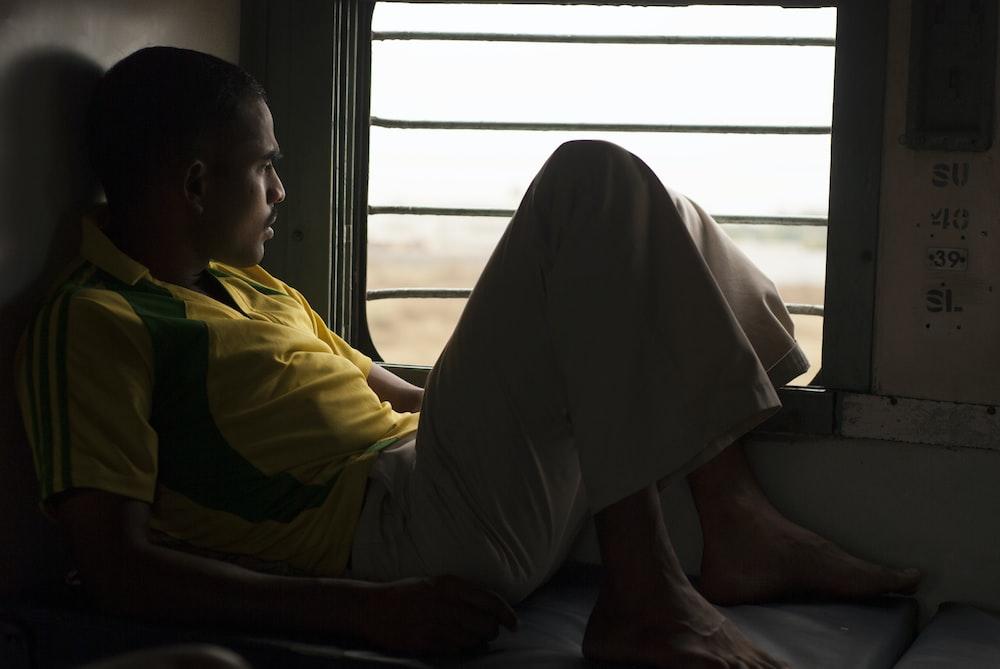 man in yellow shirt sitting on floor
