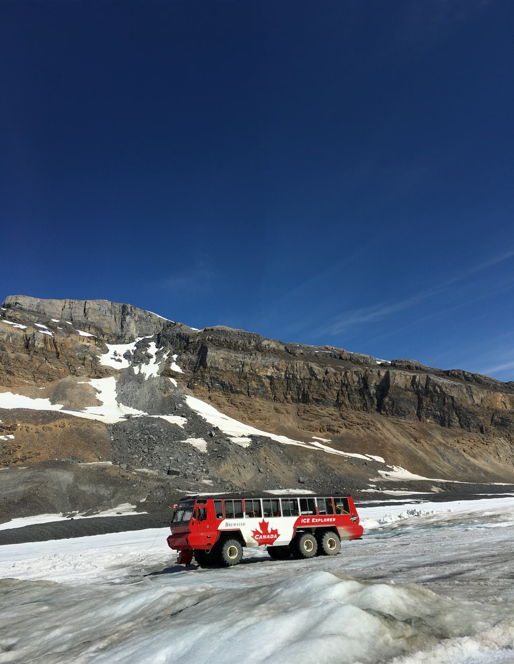 red and white car on snow covered road near rocky mountain during daytime