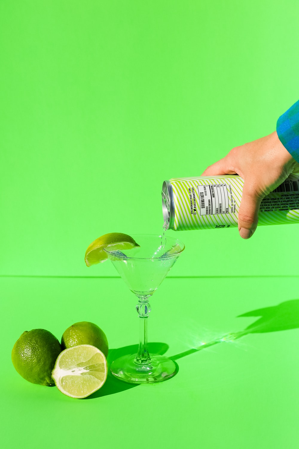 person holding clear wine glass with green liquid