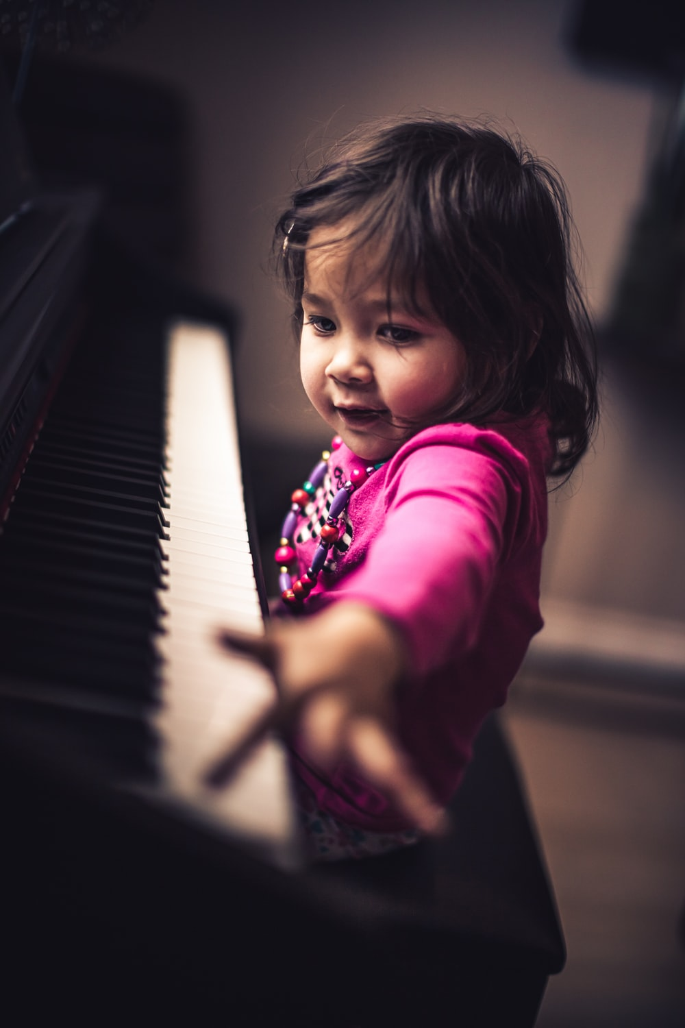girl in pink long sleeve shirt playing piano