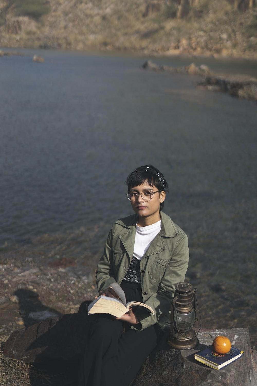 woman in green coat sitting on rock