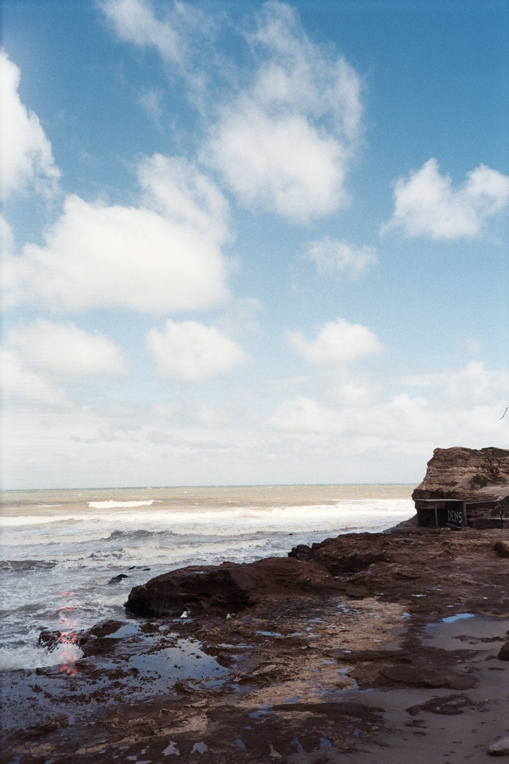 brown rock formation on sea shore under blue sky during daytime