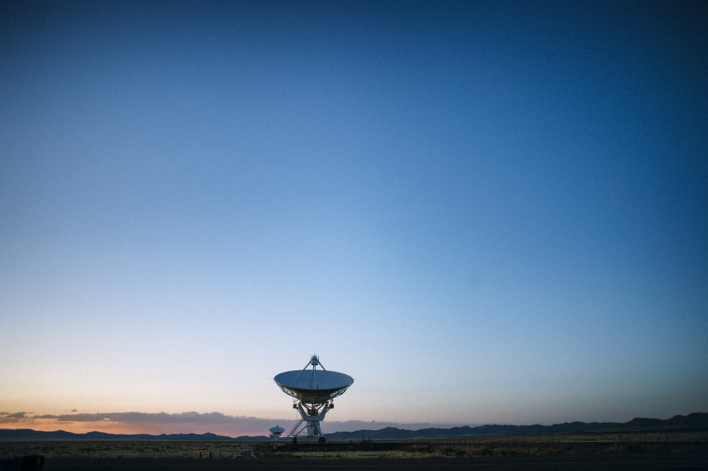 white satellite dish on brown field under blue sky during daytime
