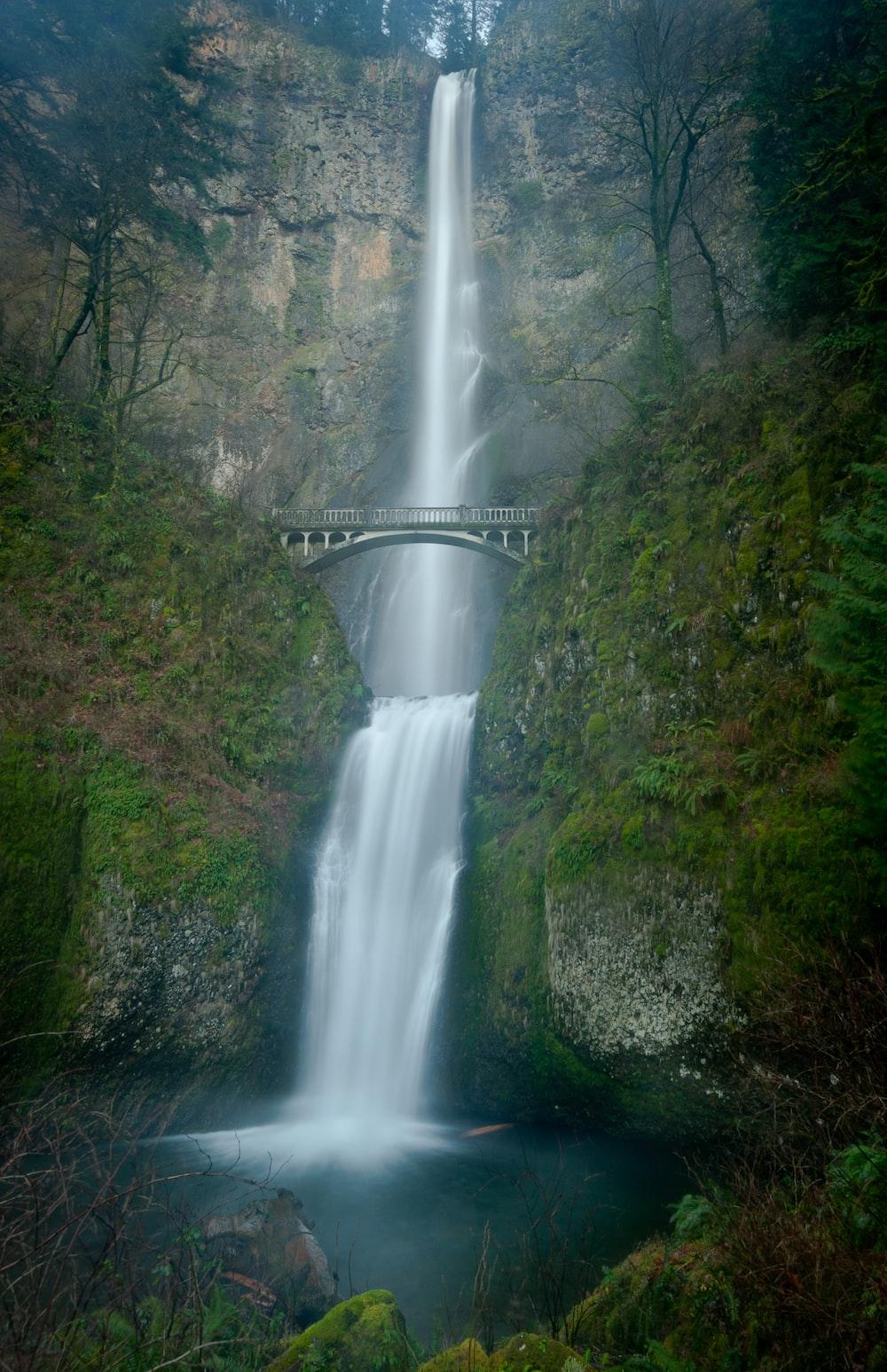 white bridge over waterfalls during daytime