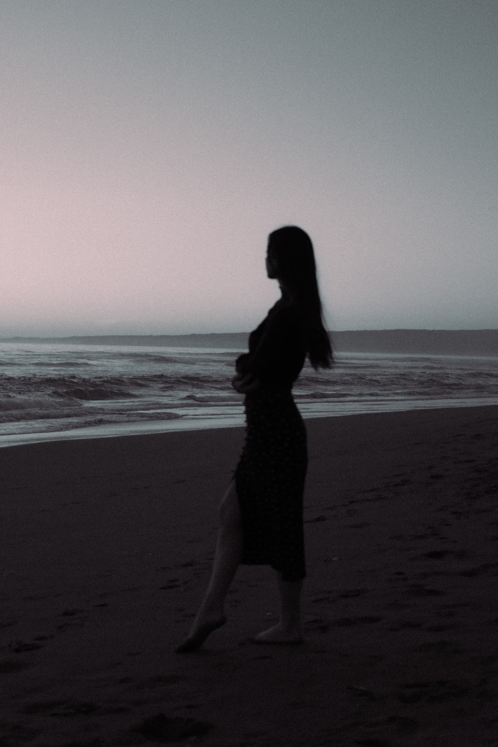 woman in black dress standing on beach during daytime