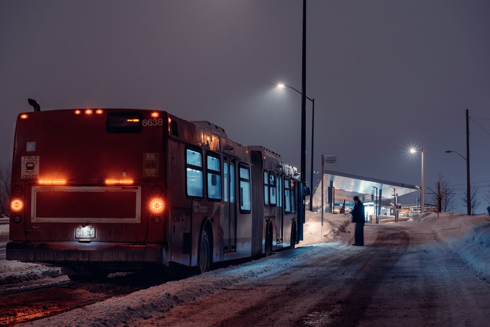 red bus on snow covered road during night time