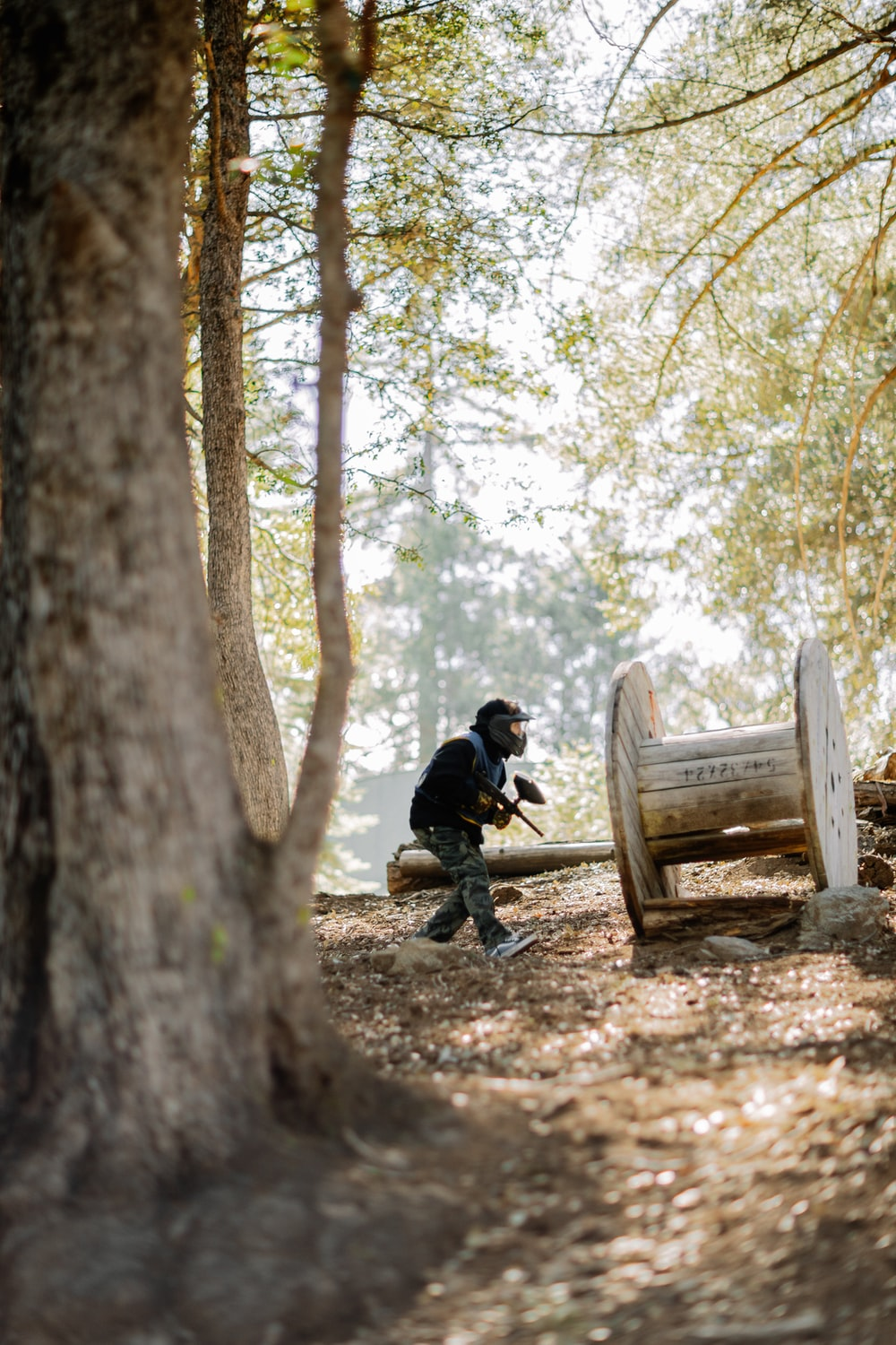 man in black jacket sitting on brown wooden bench near brown trees during daytime