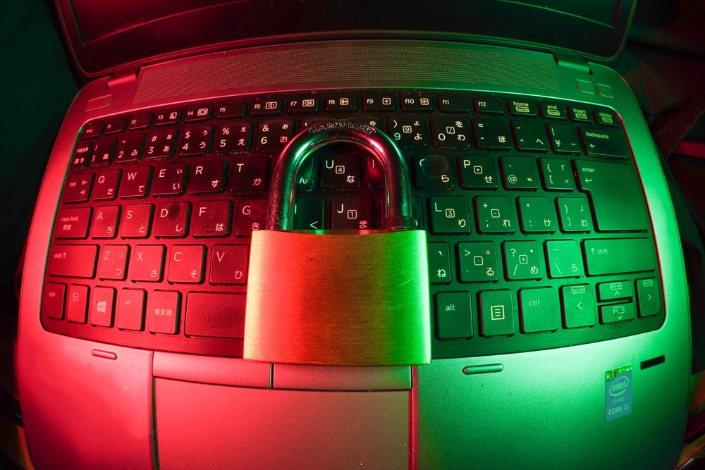 pink and silver padlock on black computer keyboard