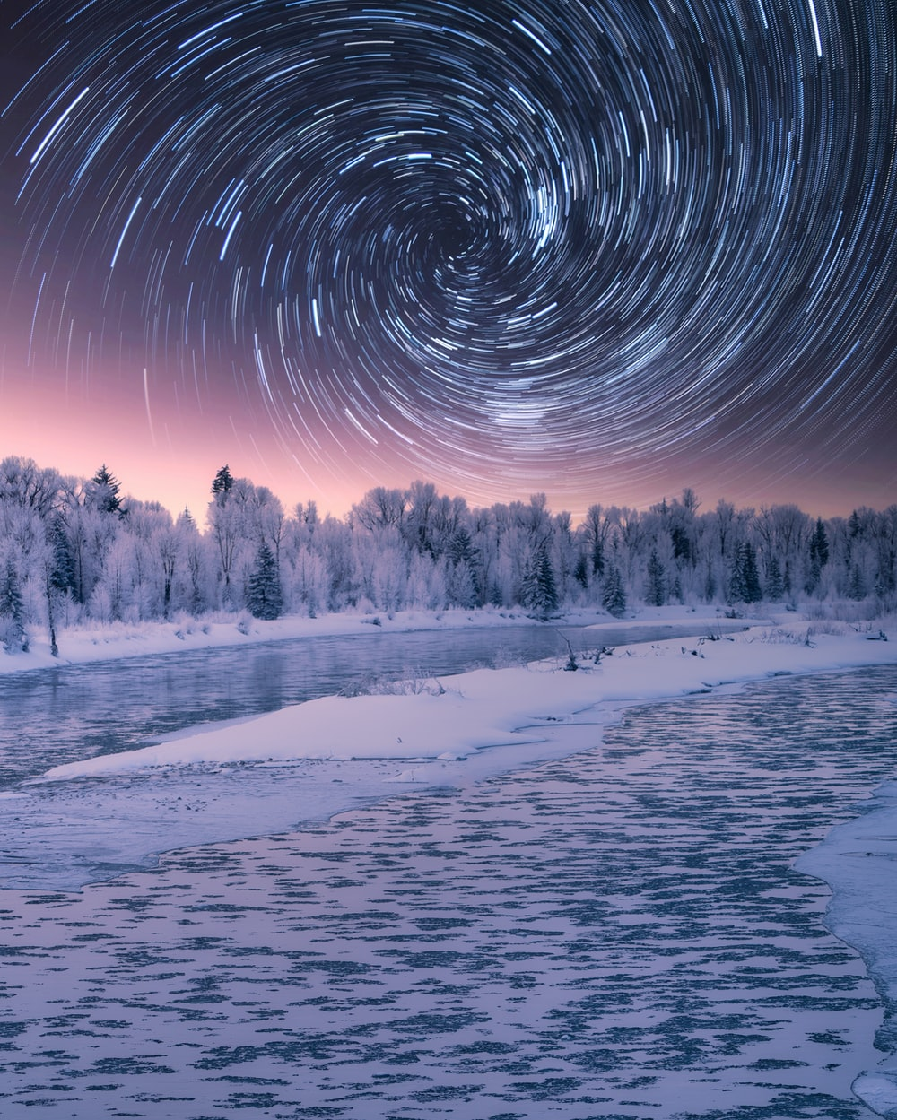 time lapse photography of stars above body of water during night time