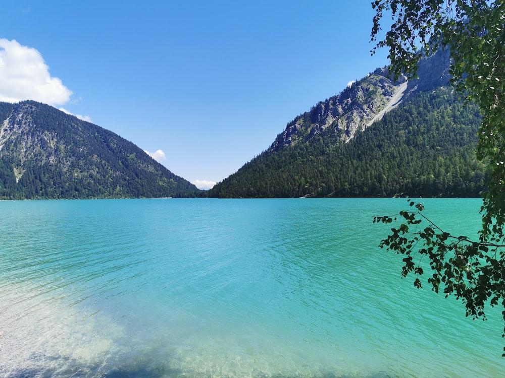 green lake near mountain under blue sky during daytime