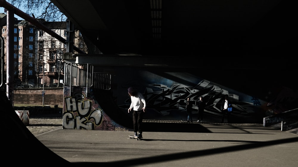 woman in white long sleeve shirt and black pants walking on sidewalk