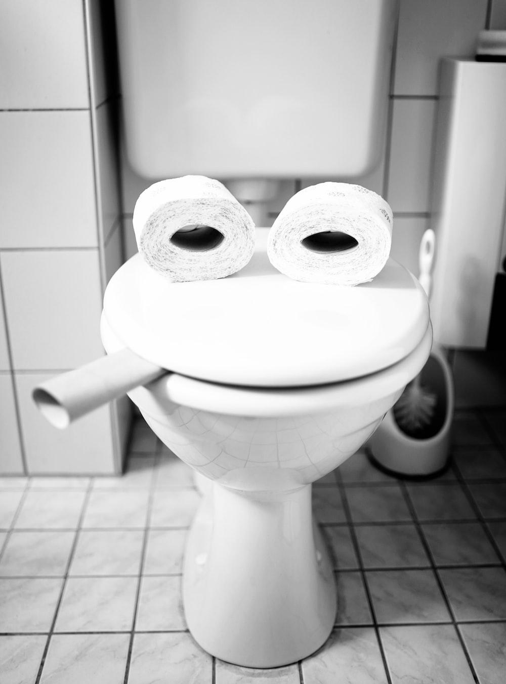 white toilet paper roll on white ceramic toilet bowl