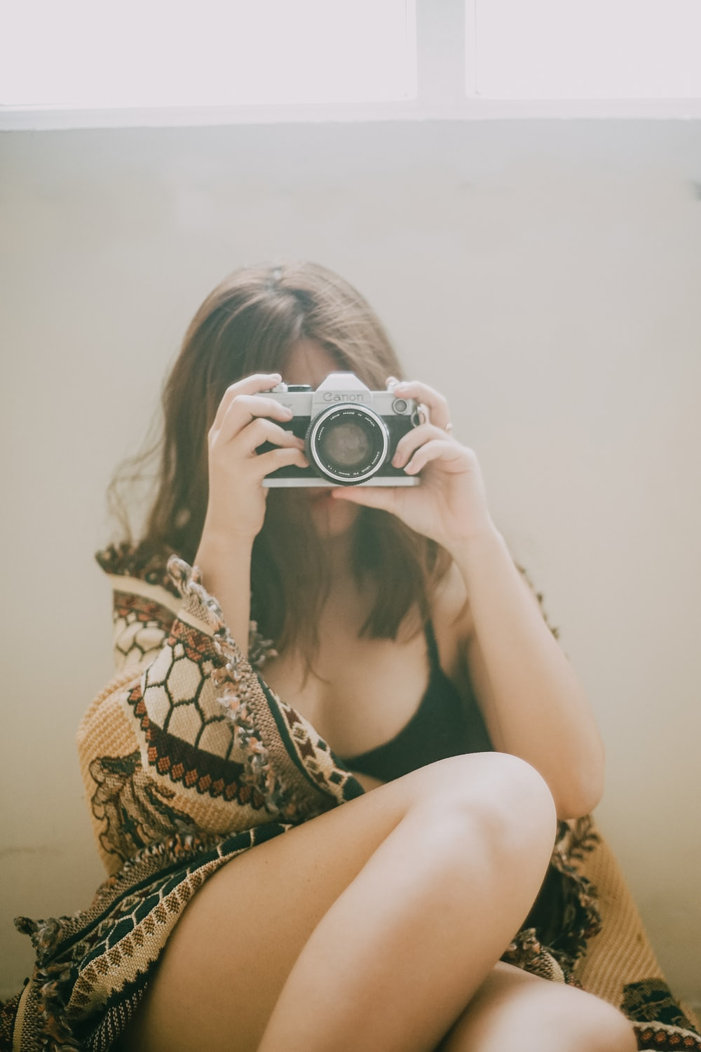 woman in black and white floral bikini top holding black and silver dslr camera