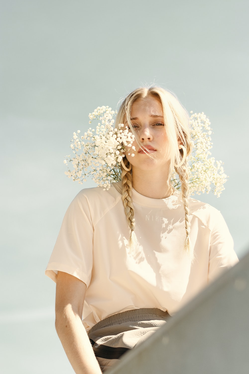 woman in white shirt with white flowers on her ear