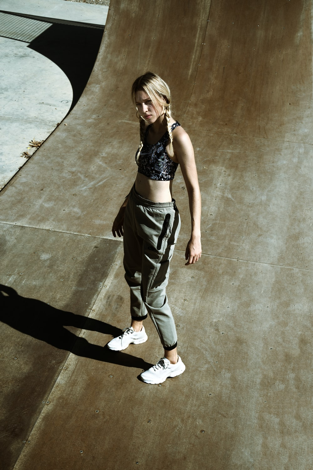 woman in black brassiere and gray pants standing on gray concrete floor