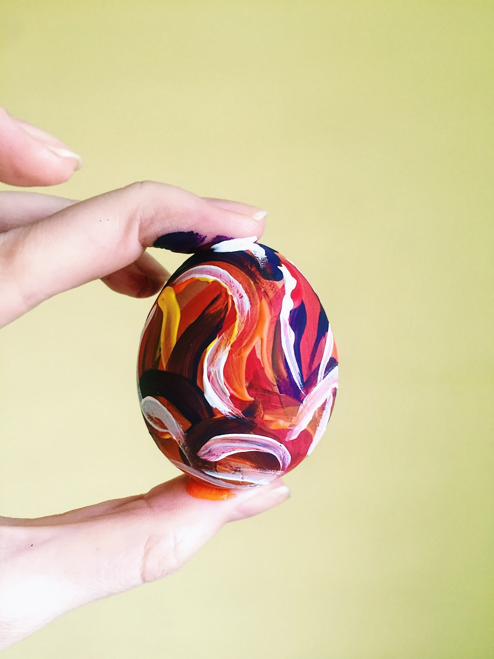 person holding red blue and yellow ball