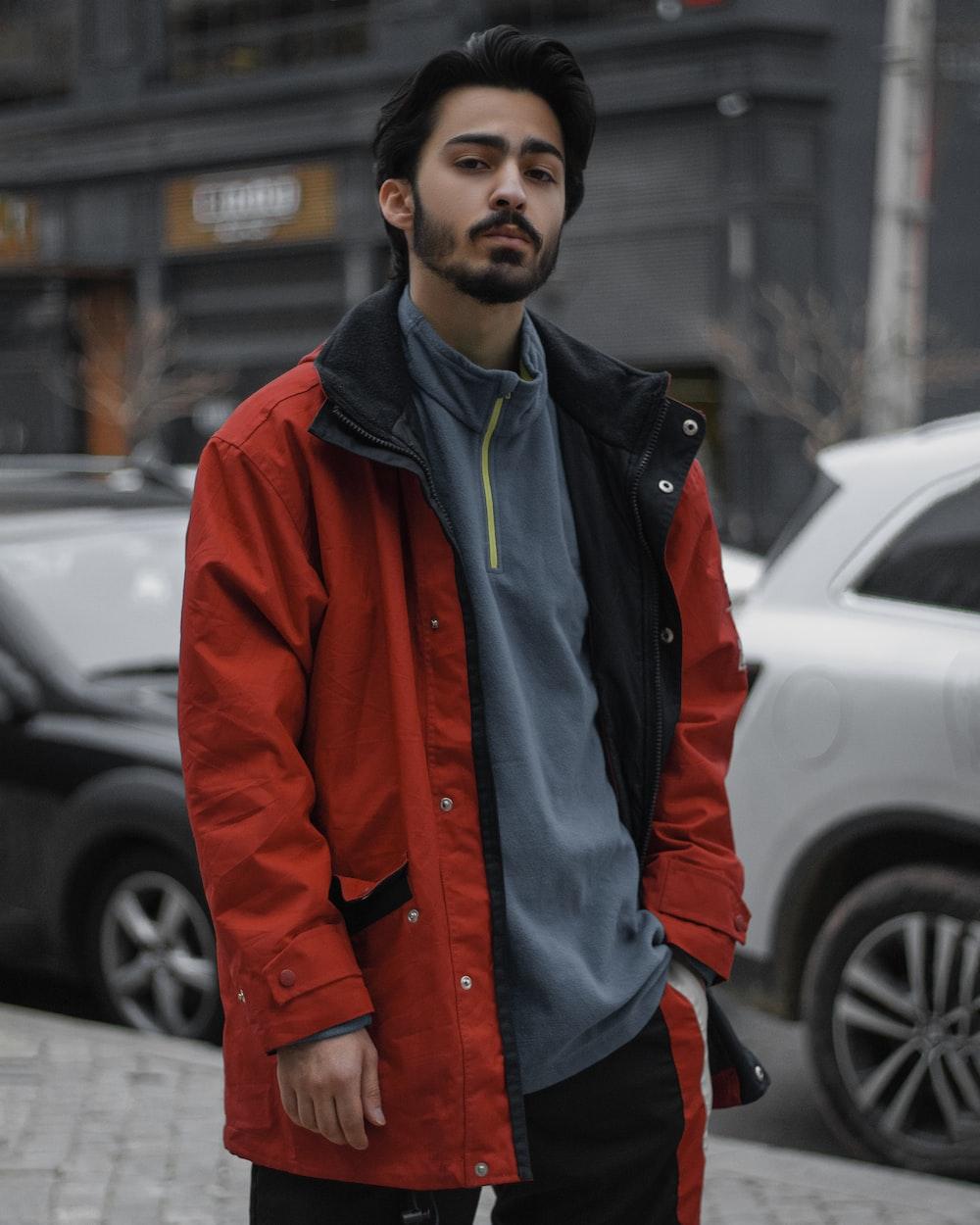 man in red jacket standing near black car during daytime