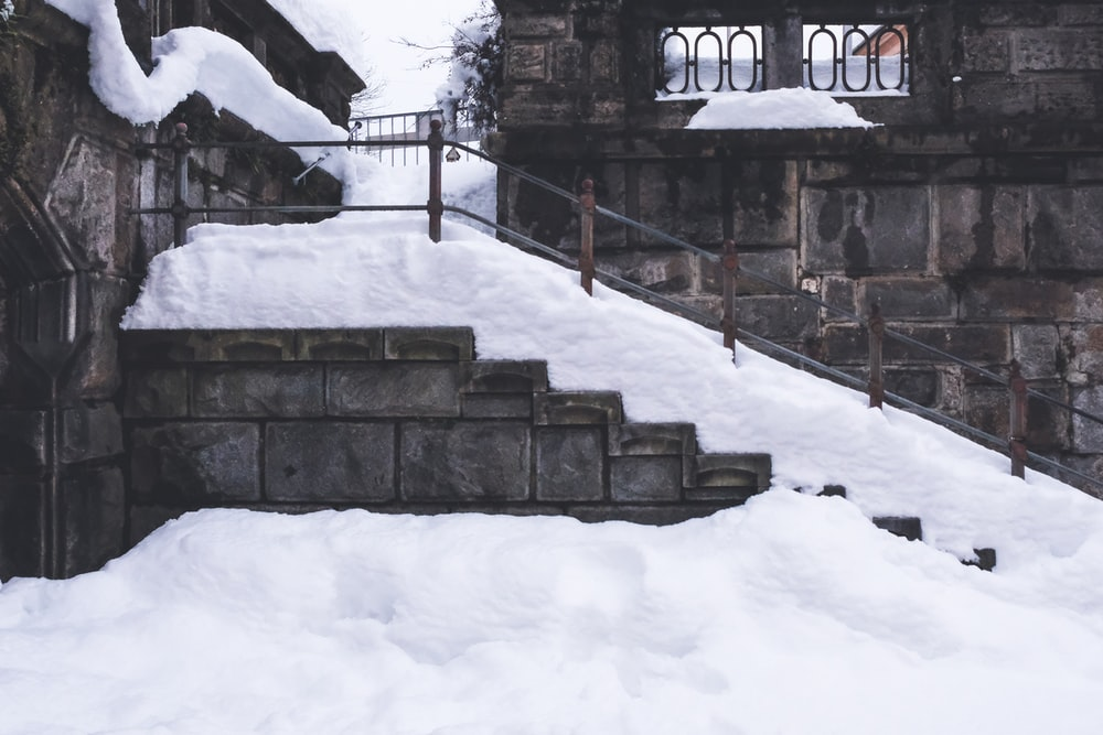 brown concrete stairs covered with snow