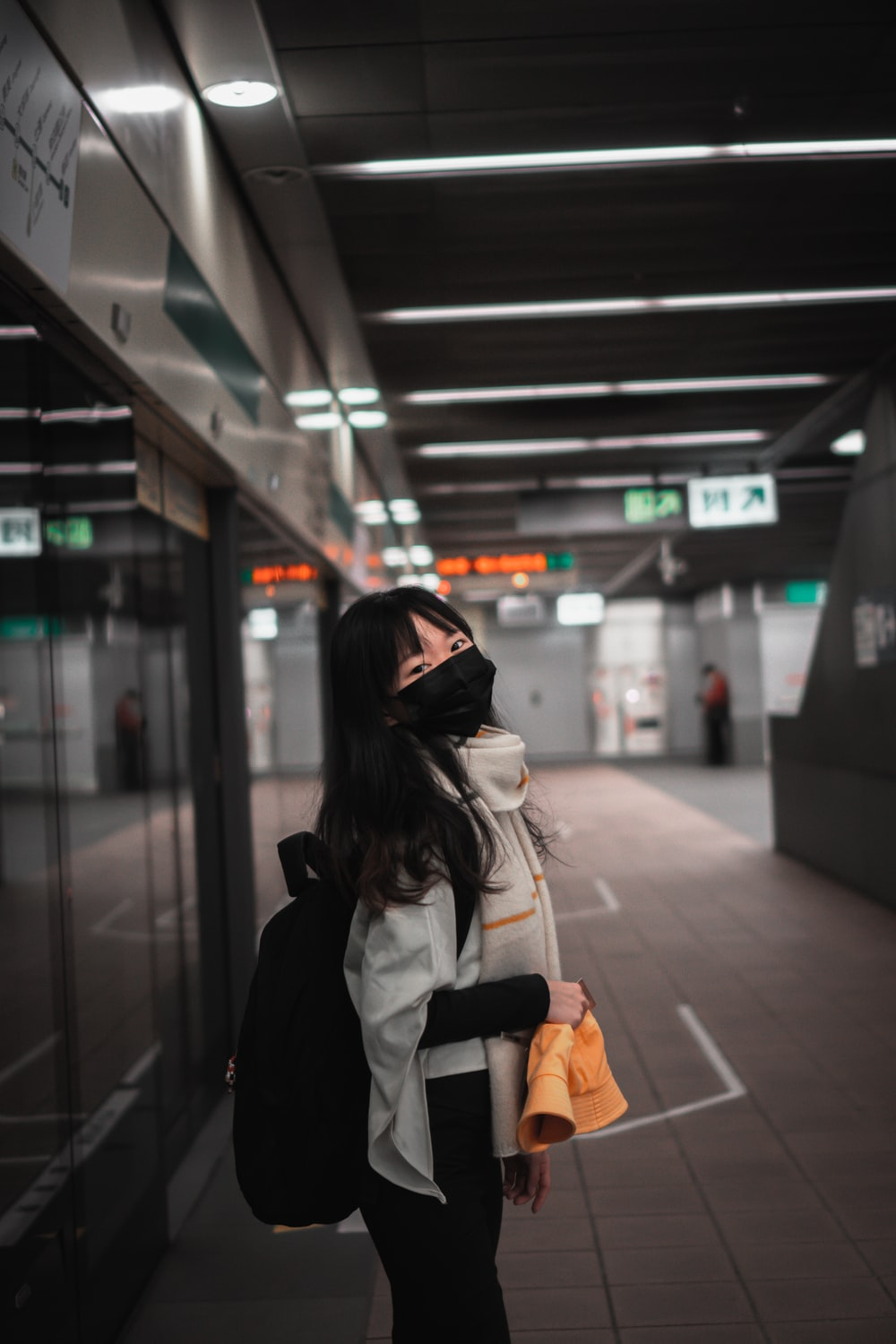 woman in black jacket and white backpack standing in train station