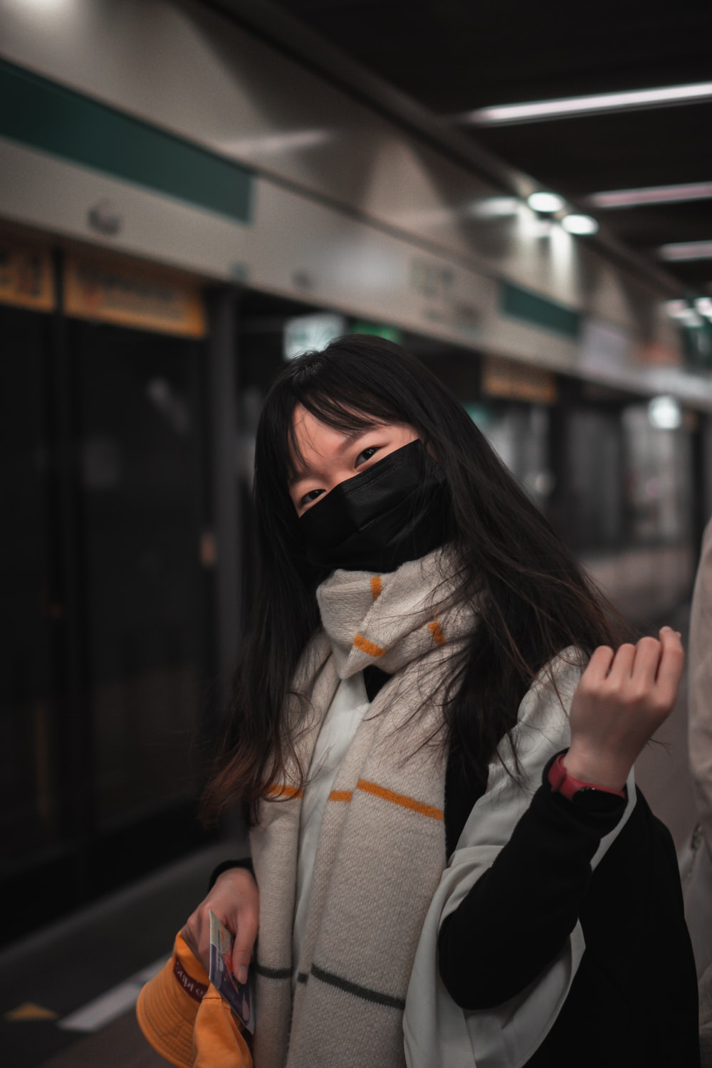 woman in black mask and gray coat