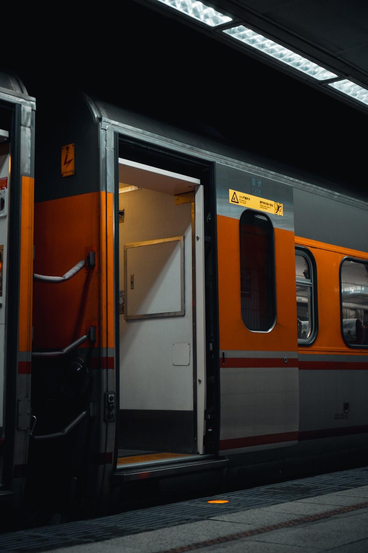 orange and black train in train station
